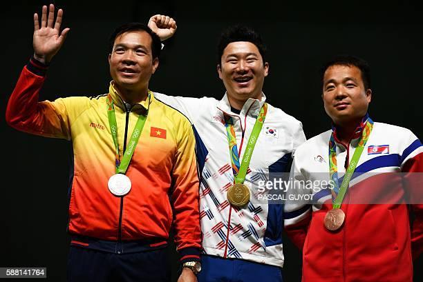 Silver medallist Vietnam's Xuan Vinh Hoang gold medal winner South Korea's Jin Jongoh and bronze medallist North Korea's Kim Song Guk stand on the...