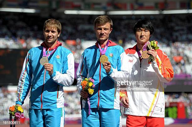 Silver medallist Vladimir Zayets of Azerbaijan gold medallist Oleg Panyutin of Azerbaijan and bronze medallist Hewei Dong of China pose on the podium...