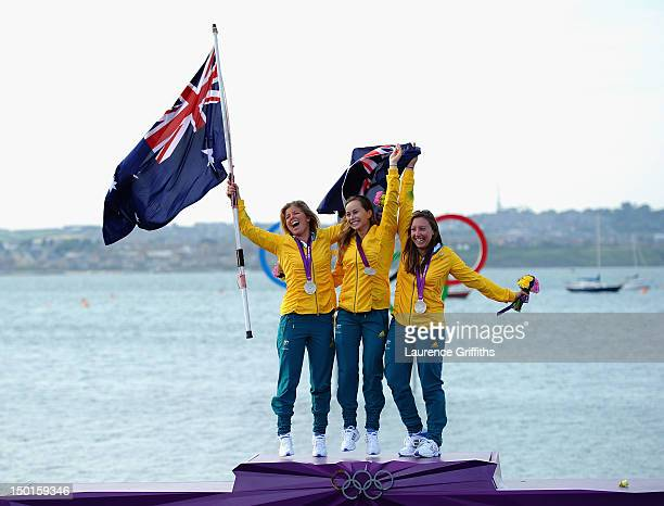 Silver medallists Nina Curtis Lucinda Whitty and Olivia Price of Australia celebrate on the podium following the Women's Elliott 6m WMR Sailing on...