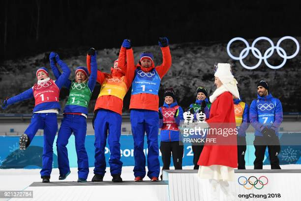 Silver medallists Norway's Marte Olsbu Tiril Eckhoff Tarjei Boe and Emil Hegle Svendsen celebrate on the podium during the victory ceremony in the...