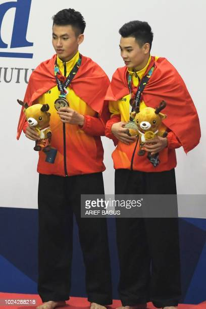 Silver medallists Vietnam's Tran Duc Danh and Le Hong Quan pose during the victory ceremony for the men's double pencak silat event at the 2018 Asian...