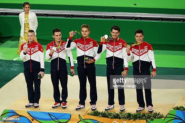 Silver medalst Russia members celebrates on the podium at the medal ceremony for the men's team final on Day 3 of the Rio 2016 Olympic Games at the...