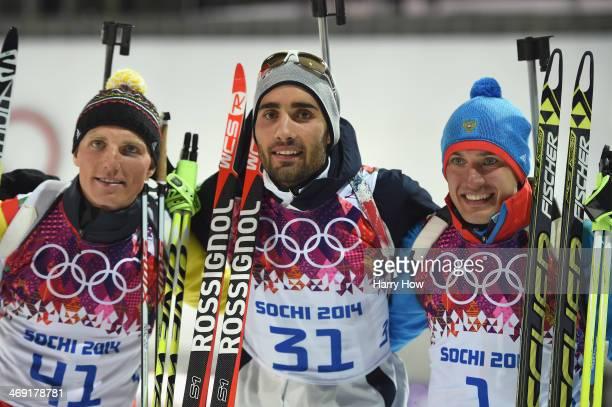 Silver medlaist Erik Lesser of Germany, gold medalist Martin Fourcade of France and bronze medalist Evgeniy Garanichev of Russia celebrate oon the...