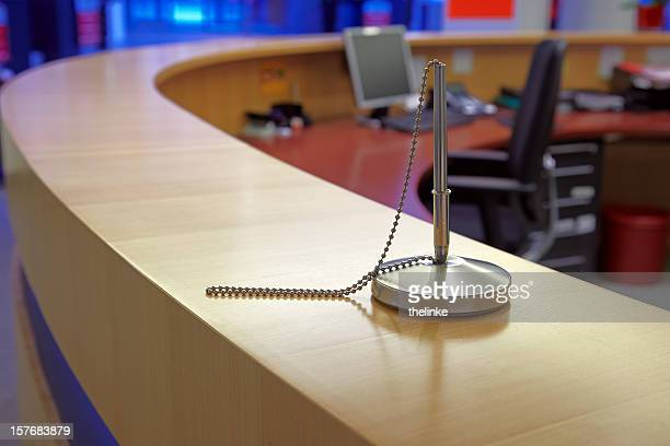 Silver pen attached to a front desk