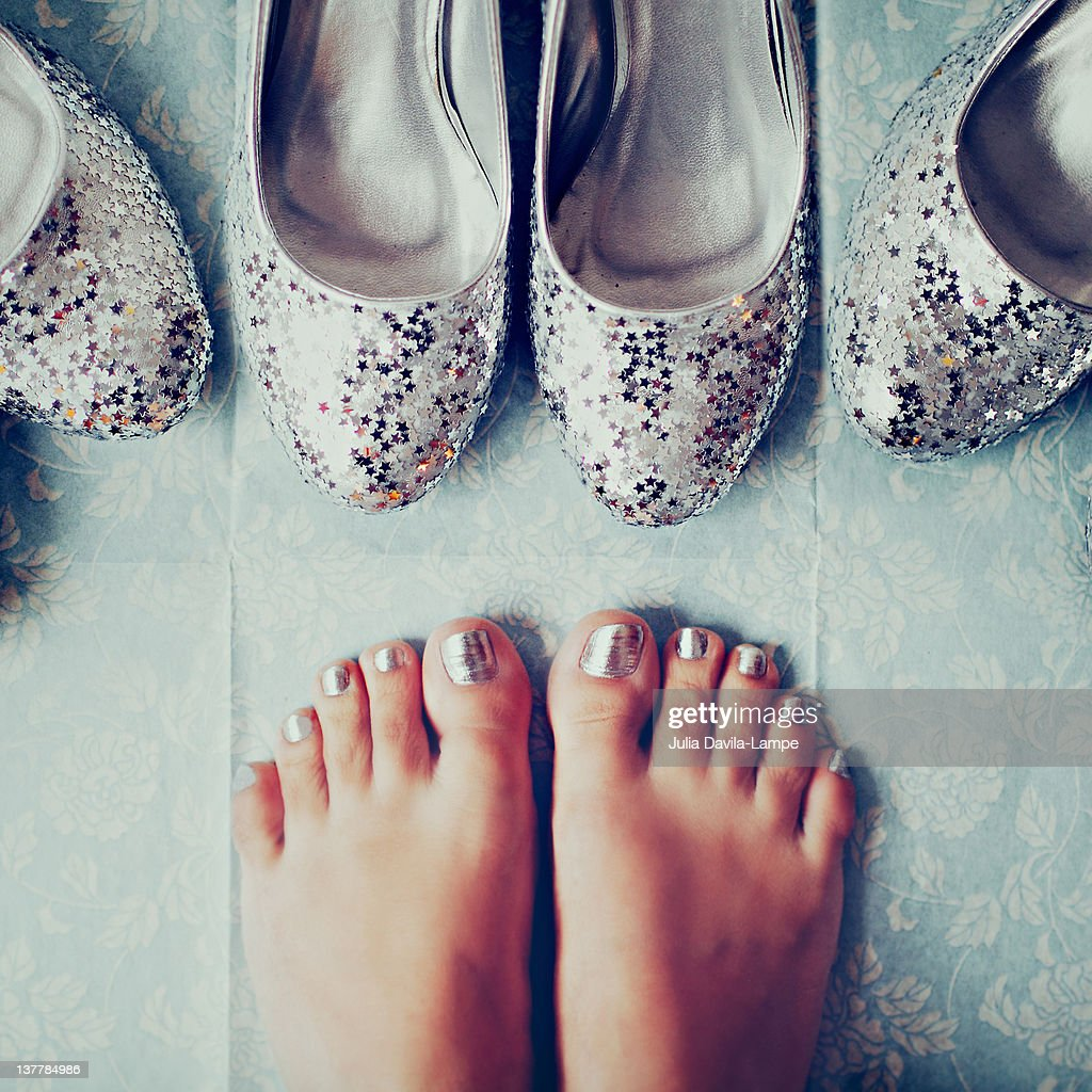 Silver plated glitter high-heels and feet : Stock Photo