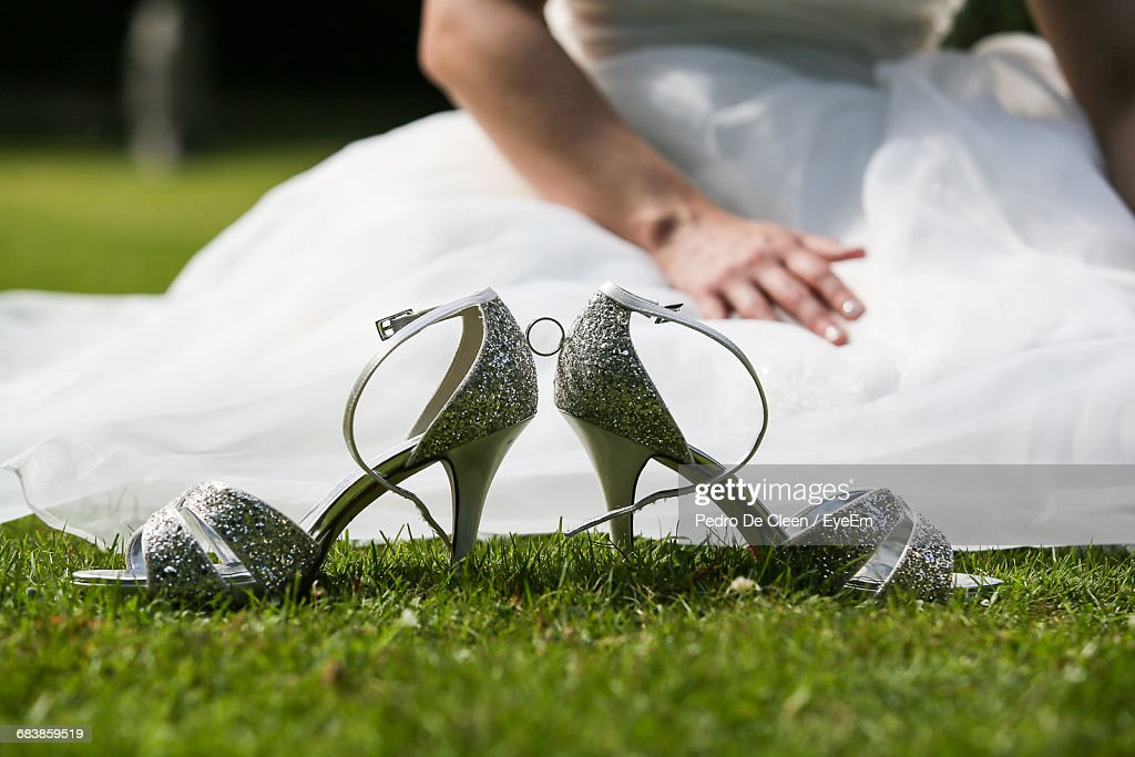 Silver Sandals Against Bride Sitting On Grass : Stock Photo