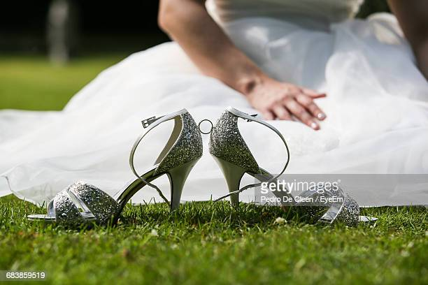 Silver Sandals Against Bride Sitting On Grass
