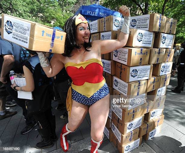 Silver Snail supporter Stephanie Nasello as Wonder Woman poses with the 100th and final box that was dropped off at the corner of Gould St and...