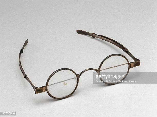 Silver spectacles with round bifocal lenses and sliding side arms made by J Hawkins Southampton England Each lens is made up of two half lenses of...