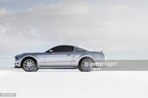 silver sports car in white landscape - van de zijkant stockfoto's en -beelden