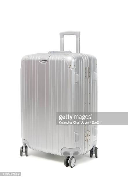 silver suitcase against white background - suitcase stock pictures, royalty-free photos & images