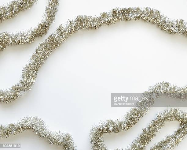 silver tinsel on a white background - tinsel stock pictures, royalty-free photos & images