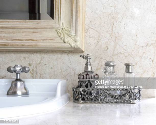 a silver tray with a collection of antique perfume bottles over a bathroom counter. still life. - 水周り ストックフォトと画像