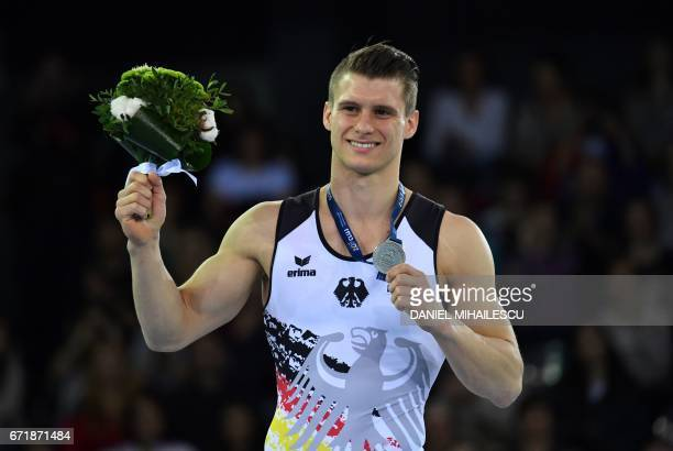 Silver winner Lukas Dauser of Germany celebrates during the medals ceremony for parallel bars of apparatus final for the European Artistic Gymnastics...