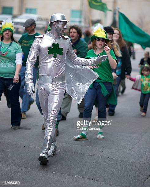 CONTENT] A silvercostume wearing man walks down the street in a St Patrick's Day parade