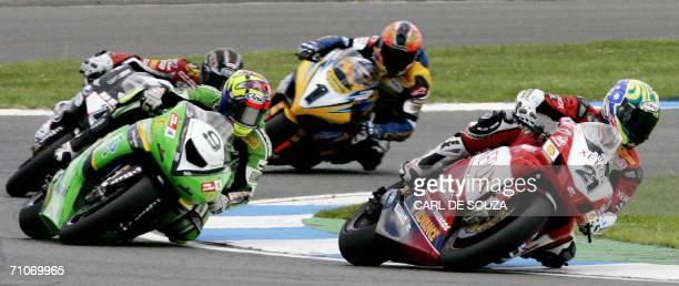 Silverstone, UNITED KINGDOM: Australian rider Troy Bayliss of the Ducati Xerox team is seen leading British rider Chris Walker, Spanish rider Ruben...