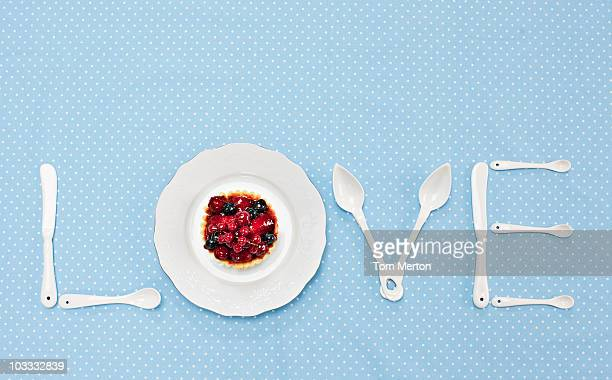 Silverware and plate with tart spelling 'love' on tablecloth