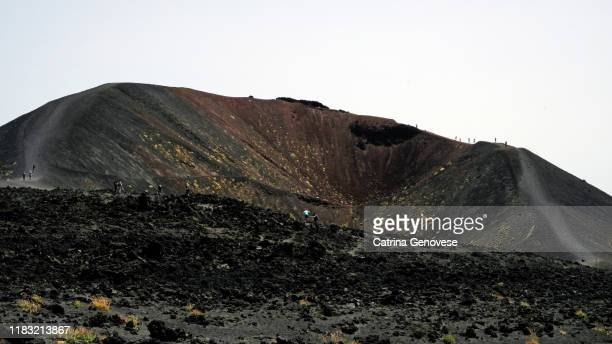 silvestri craters, lateral cones and flow form calderas,  from mount etna (volcano), sicily, italy. tourists can be seen hiking along rim of crater. - vista lateral stock pictures, royalty-free photos & images
