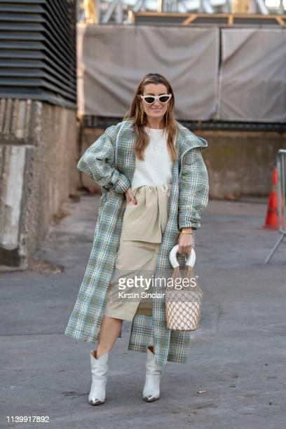 Silvia García Bartabac wears a Staud bag, Isabel Marant boots, Celine sunglasses and Dawei Studio jacket, skirt and jumper on February 26, 2019 in...