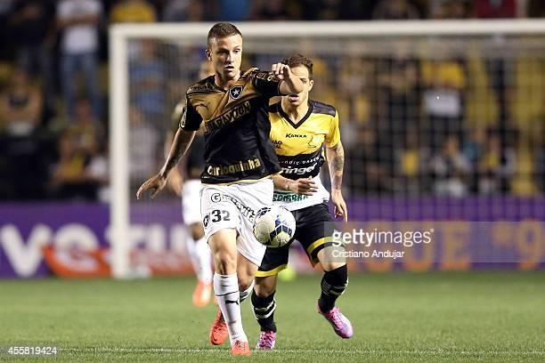 Silvinho of Criciuma run behind Sidney of Botafogo during a match between Criciuma and Botafogo as part of Campeonato Brasileiro 2014 at Heriberto...