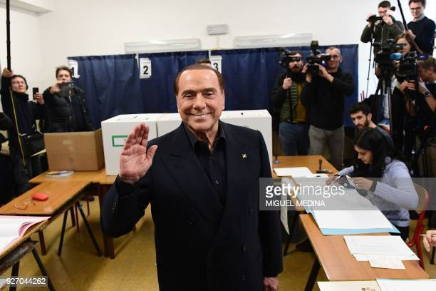 Silvio Berlusconi, leader of right-wing party Forza Italia, waves as he arrives to vote on March 4, 2018 at a polling station in Milan. Italians vote...