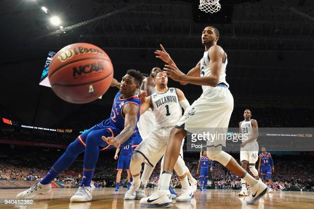 Silvio De Sousa of the Kansas Jayhawks competes for a loose ball with Jalen Brunson and Mikal Bridges of the Villanova Wildcats in the first half in...