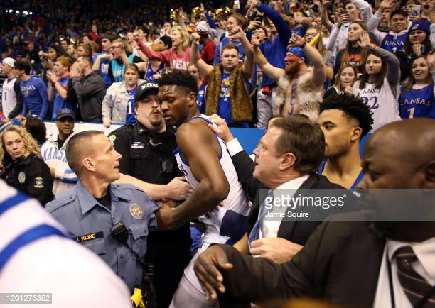 Silvio De Sousa of the Kansas Jayhawks is restrained by head coach Bill Self during a brawl as the game against the Kansas State Wildcats ends at...
