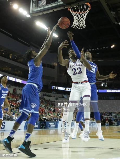 Silvio De Sousa of the Kansas Jayhawks shoots against Angel Delgado and Michael Nzei of the Seton Hall Pirates in the first half during the second...