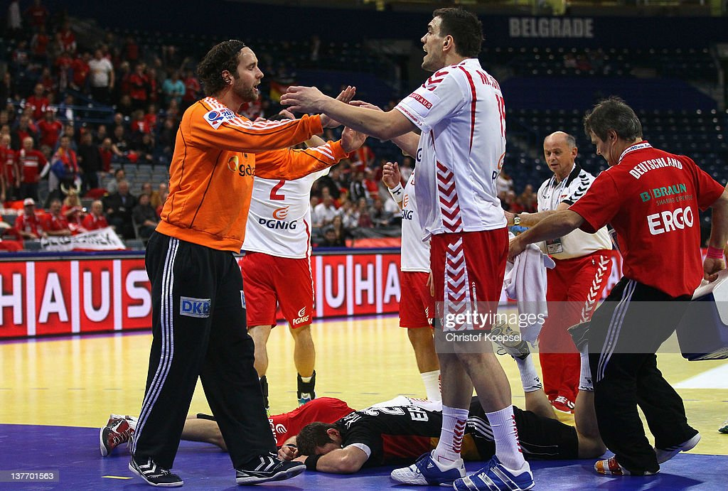 Silvio Heinevetter of Gemrany discusses with Michal Jurecki of Poland after the injury of Michael Haass of Germany (on the pitch) and Krzysztof Lijewski of Poland (on the pitch) during the Men's European Handball Championship second round group one match between Poland and Germany at Beogradska Arena on January 25, 2012 in Belgrade, Serbia.