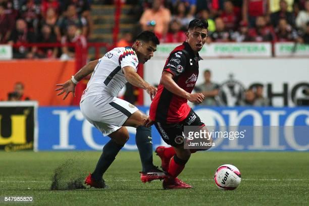 Silvio Romero of America and Joe Corona of Tijuana compete for the ball during the 9th round match between Tijuana and America as part of the Torneo...