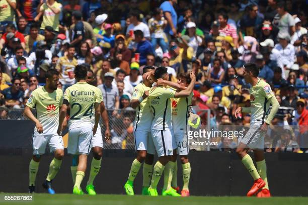 Silvio Romero of America celebrates with teammates after scoring the first goal of his team during the 11th round match between Pumas UNAM and...