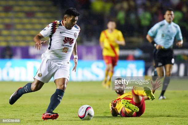 Silvio Romero of America dribbles Mario Osuna of Morelia during the seventh round match between Morelia and America as part of the Torneo Apertura...