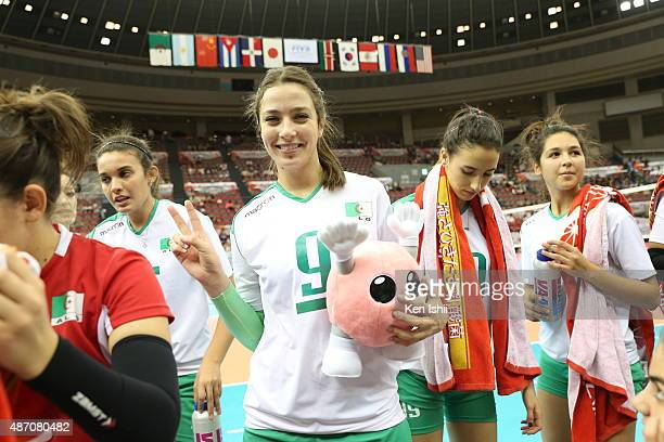Silya Magnana of Algeria poses for photographs with a mascot after the match between Russia and Algeria during the FIVB Women's Volleyball World Cup...