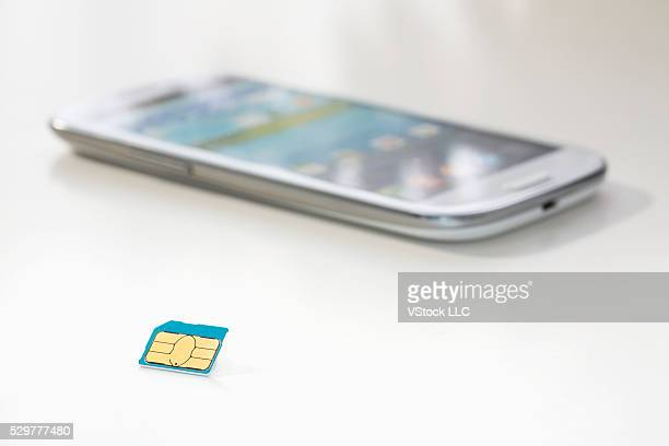 Sim card and smartphone on white
