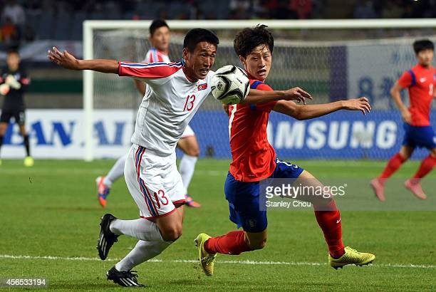 Sim Hyonjin of North Korea and Park Jooho of South Korea compete for the ballduring the Football Men's Gold Medal match between South Korea and North...