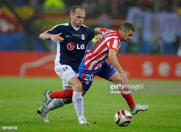 Simao of Atletico Madrid is chased by Danny Murphy of Fulham during the UEFA Europa League final match between Atletico Madrid and Fulham at HSH...