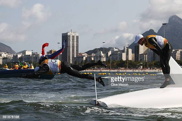 Sime Fantela of Croatia and Igor Marenic of Croatia celebrate by jumping into the sea after winning the gold medal in the Men's 470 class at the...