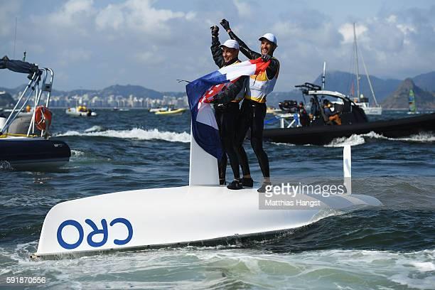 Sime Fantela of Croatia and Igor Marenic of Croatia celebrate winning the gold medal in the Men's 470 class at the Marina da Gloria on Day 13 of the...