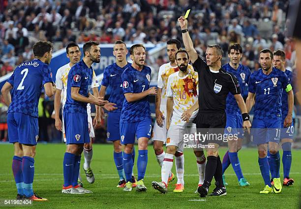 Sime Vrsaljko of Croatia is shown a yellow card by referee Bjorn Kuipers after fouling David Silva of Spain in the penalty area during the UEFA EURO...