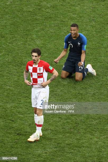 Sime Vrsaljko of Croatia looks dejected as Kylian Mbappe of France celebrates following his sides victory in the 2018 FIFA World Cup Final between...