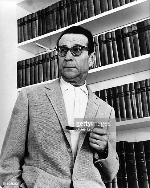 Simenon Georges *Schriftsteller Belgien Portrait mit Pfeife in der Hand vor einem Buecherregal undatiert