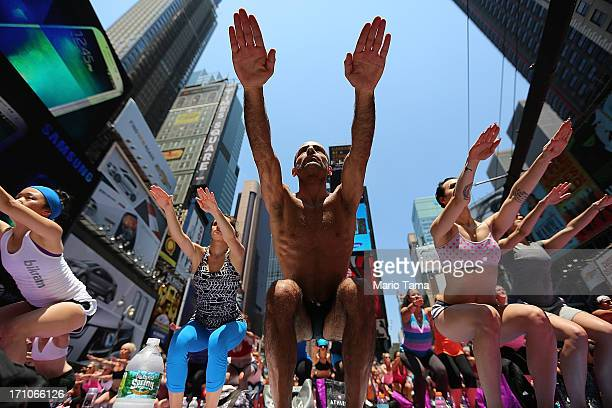 Simeone Scaramozzino and other enthusiasts perform yoga in Times Square during an event marking the summer solstice on June 21 2013 in New York City...
