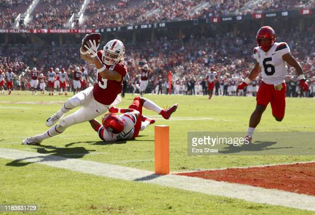 Simi Fehoko of the Stanford Cardinal dives in the a touchdown after getting past Xavier Bell and Scottie Young Jr. #6 of the Arizona Wildcats at...