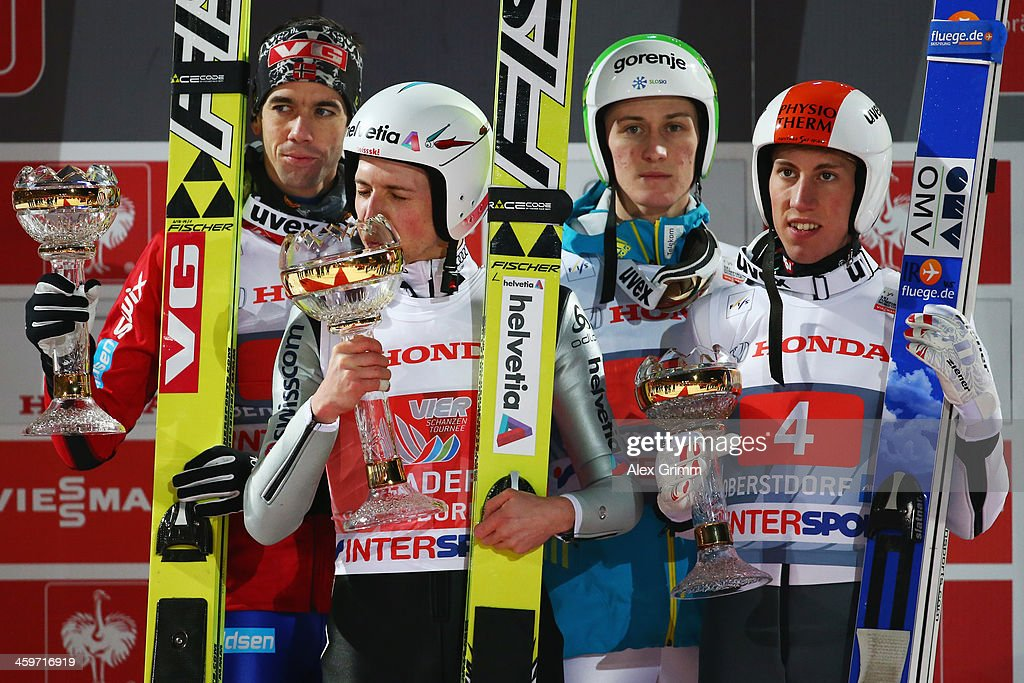 Simon Amman (front) of Switzerland celebrates after winning the Four Hills Tournament Ski Jumping event ahead of second placed Anders Bardal (L) of Norway and third placed Peter Prevc (2R) of Slovenia and Thomas Diethart of Austria (R) at Schattenberg-Schanze on December 29, 2013 in Oberstdorf, Germany.