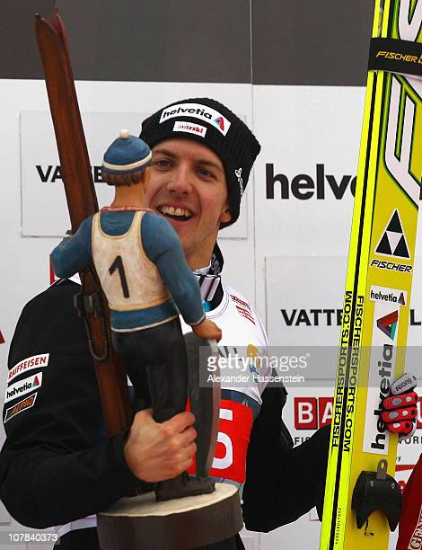 Simon Ammann of Switzerland celebrates victory with the winners present of the FIS Ski Jumping World Cup event at the 59th Four Hills ski jumping...