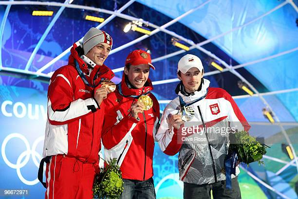 Simon Ammann of Switzerland celebrates with his gold medal and Adam Malysz of Poland and Gregor Schlierenzauer of Austria during the Medal Ceremony...