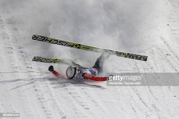 Simon Ammann of Switzerland falls on his first round jump on day 2 of the Four Hills Tournament Ski Jumping event at SchattenbergSchanze Erdinger...