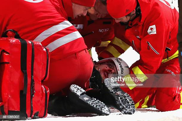 Simon Ammann of Switzerland receives medical treatment after his crash on day 8 of the Four Hills Tournament Ski Jumping event at...
