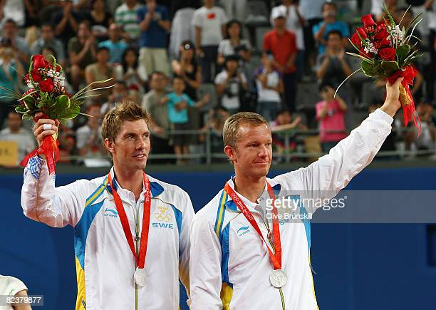 Simon Aspelin and Thomas Johansson of Sweden receive their silver medals for the men's doubles tennis at the Olympic Green Tennis Center on Day 8 of...