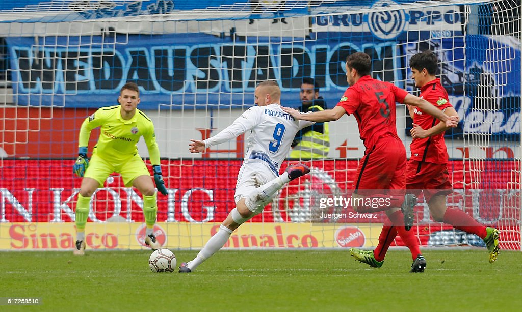 Simon Brandstetter of Duisburg (#9) kicks the ball in front of goalkeeper Marcel Schuhen of Rostock during the third league match between MSV Duisburg and Hansa Rostock at Schauinsland-Reisen-Arena on October 22, 2016 in Duisburg, Germany.